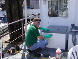 Scrubbing the decks to keep the Coastal Messenger looking new.